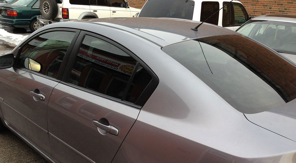 A grey sedan with tinted windows.