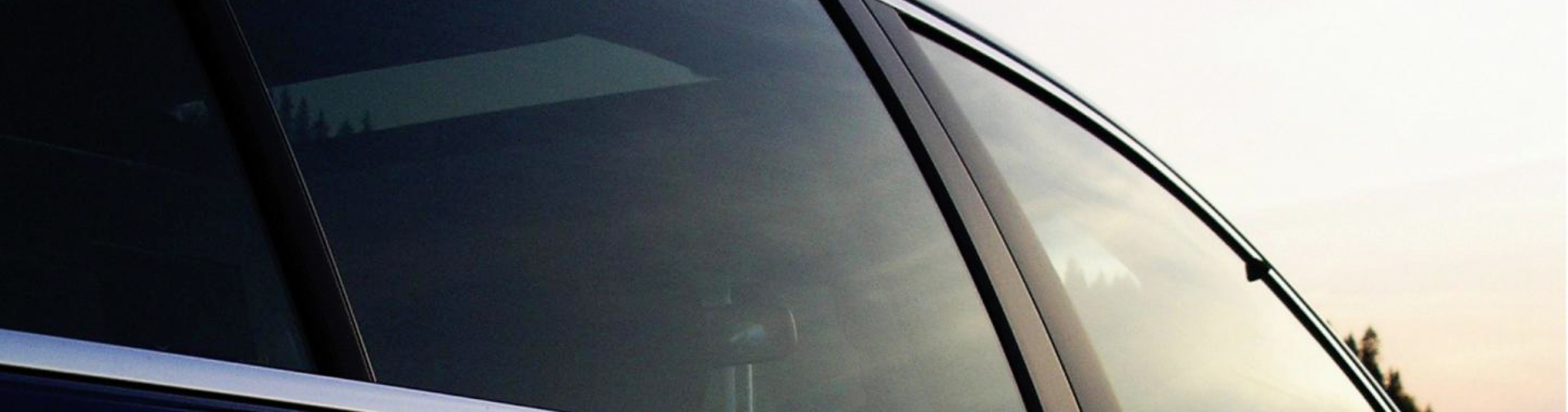 A closeup of a vehicle's tinted windows on the passenger side.